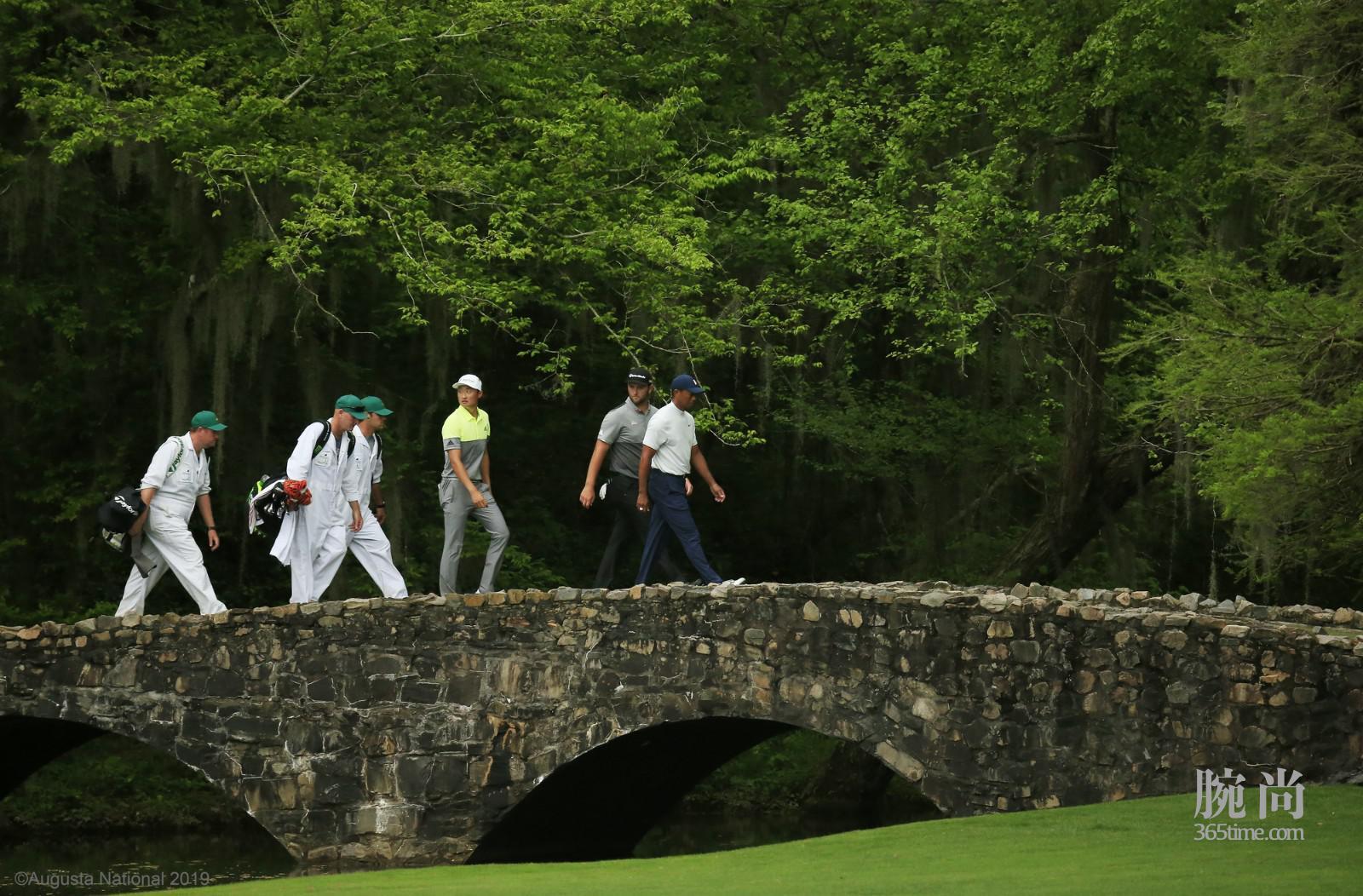 劳力士代言人泰格・伍兹、琼・拉姆及李昊桐于第二轮走过第13洞的内森桥 ©Augusta National 2019.jpg